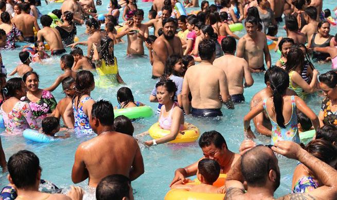 People cool off in swimming pool in Kathmandu