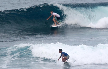 Tourists surf waves in water of Siargao Island